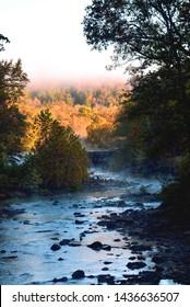 Vertical scenic shot of autumn Ozark scene with dam and fisherman in the center of photo. Taken at Devil's Den State Park in Arkansas.