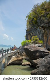 Vertical scenic shot of rocky cliff with greenery tree on the sea which the muslim women visitors walking on bridge shows beauty tourism destination for holiday vacation in Satun (Thailand) in summer.