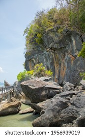 Vertical scenic shot of rocky cliff with a lot of greenery tree on the sea which the bridge was built for visitors shows beauty tourism destination for holiday vacation in Satun (Thailand) in summer.