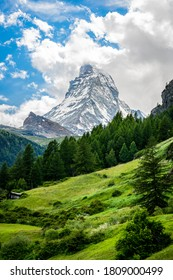 Vertical scenic view of the Matterhorn mountain summit with snow clouds blue sky and green nature during summer in Zermatt Switzerland