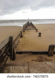 A vertical seascape view along the old wooden ruined groyne in deep sand gazing out to sea at Well Next the Sea in Norfolk East Anglia England on a cold Winter day with white clear sky with grey cloud