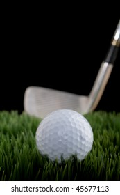 Vertical shallow focus image of a golf ball and club on grass