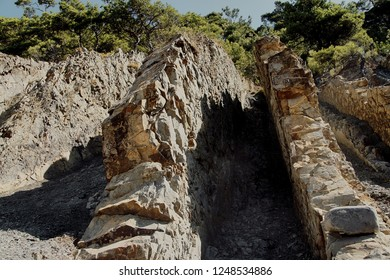 Vertical sheer cliffs with layers of sedimentary rocks of the ancient sea and pine against the blue sky. Close-up of vertical rocks with layers of Upper Cretaceous limestone and marl.