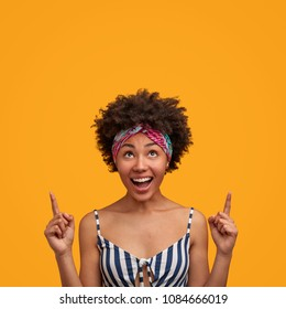 Vertical shot of adorable young lovely African American female, has positive expression, indicates with fore fingers upwards, demonstrates something wonderful at blank yellow space for your text