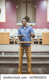 A vertical shot of an African-American male standing at the church and reading the Bible