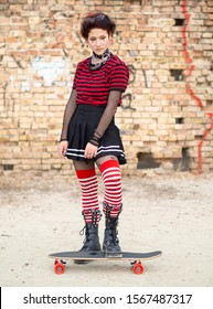 Vertical shot alternative emo girl sitting on a skate board on a brick wall background. Dark teen in a black skirt, striped stocking and steel boots