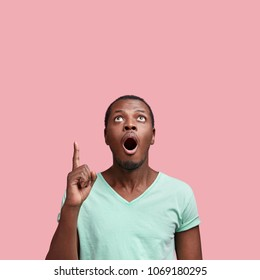Vertical shot of amazed young African American male with widely opened mouth, has unexpected expression, dressed in casual t shirt, isolated over pink background. People and advertisment concept
