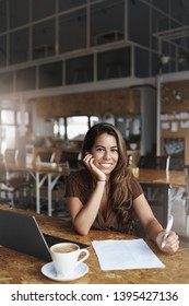 Vertical shot attractive pleasant businesswoman meet friend discuss business future investments sit co-working urban digital nomad space lean palm smiling delighted use laptop, check papers