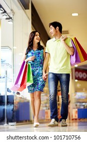 Vertical shot of attractive young people doing shopping together