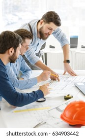 Vertical shot of a bearded male architect going through blueprints with his colleagues designers team startup developers construction architecture sketching working workplace teamwork brainstorming