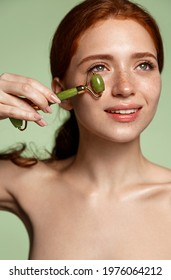 Vertical shot of beauty skincare model, redhead girl uses jade roller on healthy fresh glowing skin, self massage with tcm spa lifting tool for dark circles and puffiness, healthy beautiful face