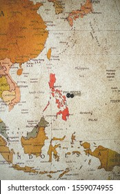 A vertical shot of a black pin on the Philippines country on the map