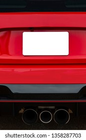 Vertical shot of a blank white license plate on the back of a red car.