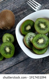 A vertical shot of a bowl filled with slices of fresh kiwi on a wooden surface