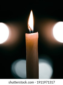 A vertical shot of a brightly burning candle against a dark blurry background