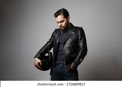 Vertical shot brutal bearded biker man wears helmet and dressed in a black leather jacket. Free space for text.