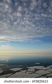 A vertical shot of a calm body of water in the late afternoon. There is ice in the foreground and clouds at the top of the frame.
