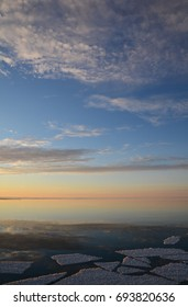 A vertical shot of a calm body of water at sunset. There is ice in the foreground and clouds at the top of the frame.