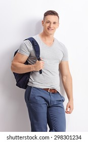 Vertical shot of a casual male student with a blue backpack leaning against a wall and looking at the camera