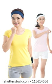 Vertical shot of cheerful female joggers keeping fit