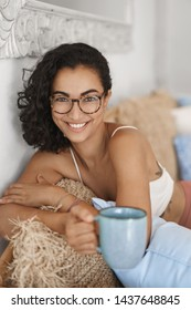 Vertical shot cheerful smiling happy young woman glasses lying sofa drink coffee hold mug grinning gazing sassy camera having funny foreplay conversation boyfriend spend summer weekends indoors