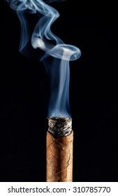 Vertical shot with cigar smoke rising from the burning Toback