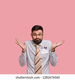 Vertical shot of clueless doubtful Caucasian man with thick stubble has uncertain look, wears formal shirt and tie, tries to make decision, poses over pink background with blank space for information