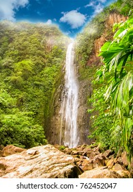 Vertical shot of the colorful Carbet Falls or Les Chutes du Carbet in Basseterre, french tropical rainforest of Guadeloupe island on blue sky day, French Caribbean and greatest Guadeloupe attraction.