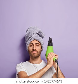 Vertical shot of confident unshaven man raises electric fan, wears towel on head, going to dry hair, dressed in casual clothes, stands against over purple wall with empty space for your advertising
