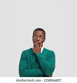 Vertical shot of contemplative thoughtful dark skinned man keeps hand under chin, looks thoughtfully upwards, dressed in green sweater, poses over white background with free space for your text