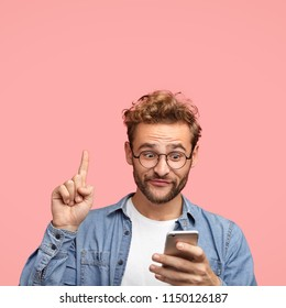 Vertical shot of curious male has appealing appearance, raises fore finger, looks with great interest at smart phone, reads relevant news in internet, isolated over pink background with copy space