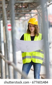 Vertical shot of cute female engineer with helmet and safety jacket on construction site