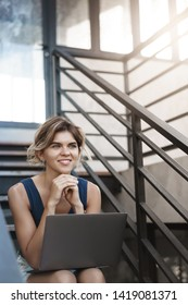 Vertical shot dreamy ambitious good-looking blond young girl student sit outdoor stairs lean hands look aside smiling happily relaxing hold laptop knees inspired create awesome freelance project work