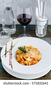 Vertical shot of Duck Ragu With Pappardelle  and a glass of red wine