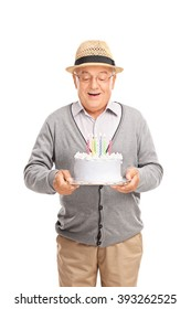 Vertical shot of an excited senior gentleman blowing candles on a birthday cake isolated on white background