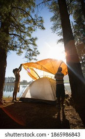Vertical shot of a father and son assembling an orange tent at a lakeside camping trip.