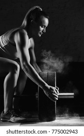 Vertical shot a female crossfit athlete preparing barbell for weightlifting at the gym magnesia protection powerlifting crossfit fitness strength athletics workout preparation focusing concentration