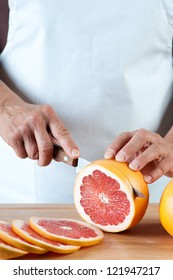 Vertical shot of female hands slicing a fresh grapefruit