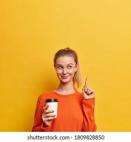 Vertical shot of happy pleased European woman wears casual orange jumper, transparent glasses, points above on copy space, holds takeaway drink, isolated over yellow background. Your promo here