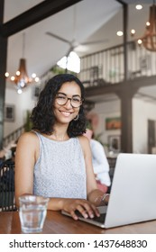 Vertical shot hardworking motivated young female student preparing exam writing essay co-working place urban cafe sit wooden table drink watter working laptop smiling joyfully wear glasses
