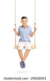 Vertical shot of a joyful little boy sitting on a swing and looking at the camera isolated on white background