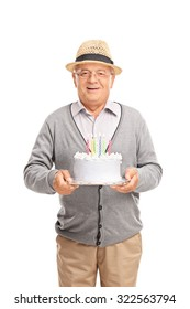Vertical shot of a joyful senior gentleman holding a birthday cake and smiling isolated on white background