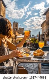 A vertical shot of a lady having breakfast in a cafe near a castle in Navarra, Spain