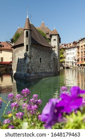 A vertical shot of the Le Palais de I'lle with purple flowers in the foreground in Annecy, France
