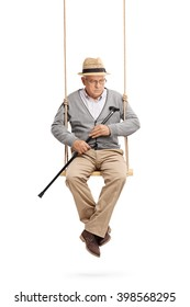 Vertical shot of a lonely and depressed senior man sitting on a swing and looking down isolated on white background