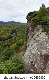 A vertical shot looking down on a river winding through trees on the left and a rock wall on the right.  The Porcupine Mountains in the Upper Peninsula of Michigan.
