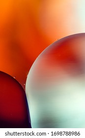 Vertical shot of macro bubbles with backlight and red and orange background