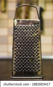 A vertical shot of a metal food grater on a table