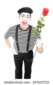 Vertical shot of a mime artist holding a red rose isolated on white background