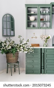 Vertical shot of monochrome kitchen counter with drawers and white top, hanging cabinet with glass doors, bowls and mugs, flowers in jar and woven bucket, vintage furniture, mirror with window shape